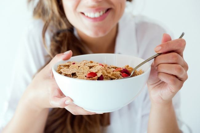 Portrait of young woman in underwear eating cereals. Isolated on white.