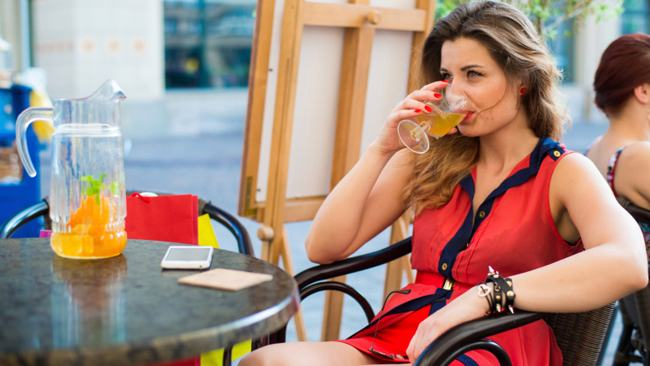 Sensual young woman with drink sitting in a cafe.