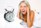 Frustrated woman covering ears as alarm clock rings
